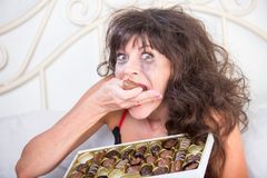 Manic Woman Crying and Eating Chocolates in Bedroom. Manic mature woman crying and eating chocolates in her bedroom Royalty Free Stock Images