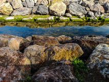 Manica con le rocce su entrambi i lati e sulle riflessioni in acqua immagini stock