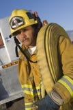 Manichetta antincendio di trasporto del combattente di fuoco sulla spalla fotografia stock libera da diritti