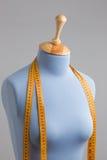 Manichino blu del sarto con nastro adesivo di misurazione accanto alla parete Fotografia Stock Libera da Diritti