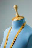 Manichino blu del sarto con nastro adesivo di misurazione accanto alla parete Fotografie Stock Libere da Diritti