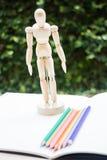 Manichino di legno che sta sul paperbook del disegno dell'artista Fotografie Stock