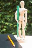 Manichino di legno dell'artista che sta con la matita di colore Fotografie Stock Libere da Diritti