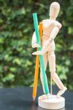 Manichino di legno dell'artista che sta con la matita di colore Immagini Stock