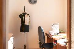 Manichino nero, tavola con la macchina per cucire e sedia blu in studio di cucito fotografia stock