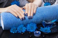 Manicura azul hermosa con el crisantemo y toalla en la tabla de madera negra Spa Foto de archivo libre de regalías