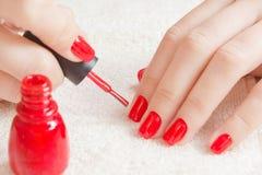 Manicura - clavos manicured hermosos del ` s de la mujer con el esmalte de uñas rojo en la toalla blanca suave Fotos de archivo libres de regalías