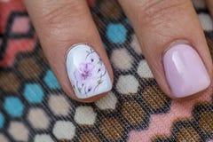 Manicura de la primavera Blanco de la manicura rosa de la manicura flor rosada de dibujo en el clavo blanco del fondo fondo 'pana fotografía de archivo