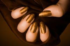 Manicura de oro brillante de los clavos Imágenes de archivo libres de regalías