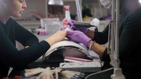 Manicura en la tienda de belleza - amo cosmético en pulimento médico de los tratos de la máscara en los clavos almacen de metraje de vídeo