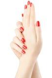 Manicura en las manos femeninas con el esmalte de uñas rojo Fotografía de archivo libre de regalías