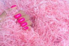 Manicura femenina de moda elegante Clavos rosados plásticos de neón en fondo del confeti fotos de archivo libres de regalías
