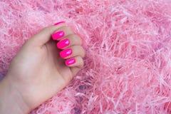 Manicura femenina de moda elegante Clavos rosados plásticos de neón en fondo del confeti imagen de archivo