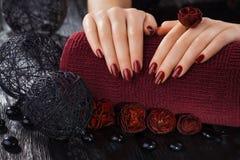 Manicura roja en la tabla de madera negra Foto de archivo libre de regalías