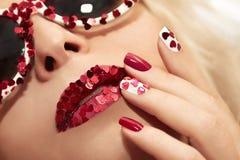 Manicura y labios con los corazones Imagen de archivo