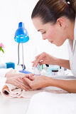Manicure. A salon manicurist giving a woman a manicure at her station Royalty Free Stock Photo