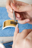 Manicure. The master puts a brush a material for escalating of nails royalty free stock image