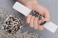 Manicure. Beautiful hand with fresh manicured stylish nails holding a file Stock Photography
