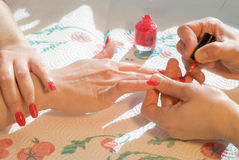 Manicure. Woman applying red nail polish royalty free stock photos