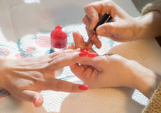 Manicure. Woman applying red nail polish stock photo