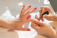 Manicure. Woman applying red nail polish stock images