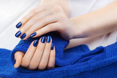 Manicure with ablue knitted scarf Stock Image