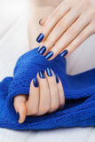 Manicure with ablue knitted scarf Royalty Free Stock Image