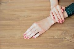 Manicure alla moda alla moda Mani di bella giovane donna su un fondo di legno Fuoco selettivo Copi lo spazio fotografia stock libera da diritti