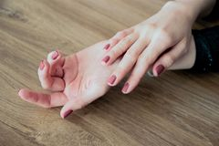Manicure alla moda alla moda Mani di bella giovane donna su un fondo di legno leggero Fuoco selettivo sfuocatura fotografia stock libera da diritti