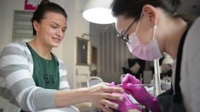 Manicure alto vicino dell'hardware in un salone di bellezza Trapano elettrico dell'archivio di unghia di uso del manicure al mani stock footage