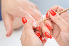Manicure applying - cleaning the cuticles Royalty Free Stock Photo