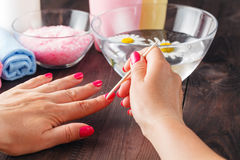 Manicure applying, cleaning the cuticles with wooden stick Royalty Free Stock Images
