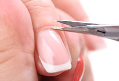 Manicure applying - cutting the cuticle. Beauty salon, manicure applying, cutting the cuticle with scissors stock photo