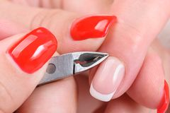 Manicure applying - cutting the cuticle. Beauty salon, manicure applying, cutting the cuticle with scissors royalty free stock photography