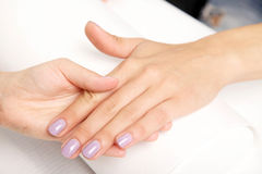 Manicure - Beautiful manicured woman's nails with violet nail po Royalty Free Stock Photography