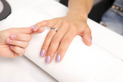 Manicure - Beautiful manicured woman's nails with violet nail po Royalty Free Stock Image
