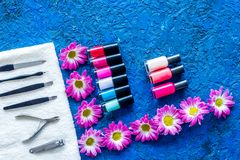 Manicure in beauty salon. Tools for manicure, nail polishes and towels on blue desk top view copyspace Stock Image
