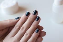 Manicure blu scuro misero Smalto liso Mani della donna sulla tavola bianca Fotografia Stock
