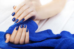 Manicure with blue knitted scarf Stock Photo