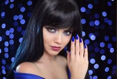 Manicure. Blue makeup. Beautiful brunette woman face close up po Royalty Free Stock Photo