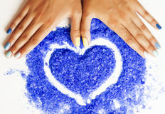 Manicure with blue nails and seasalt close up like heart, love f. Manicure with blue nails and seasalt close up like heart,  in love for summer Royalty Free Stock Photo