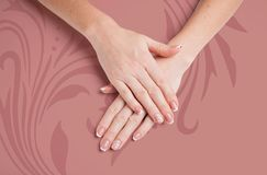 Manicure bonito Mãos de uma mulher em um fundo da cor da terracota com um teste padrão floral imagens de stock royalty free