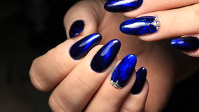 Manicure, cat`s-eye and blue stained glass gel polish with a picture and rhinestones Royalty Free Stock Photo