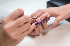 Manicure che rimuove cuticola con lo spingitoio del metallo Fotografie Stock Libere da Diritti