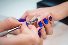 Manicure che rimuove cuticola dal chiodo della ragazza Immagini Stock