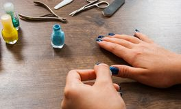 Manicure. Closeup of a woman hand painting her nails with nail polish on a wooden Royalty Free Stock Photo