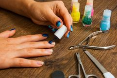 Manicure. Closeup of a woman hand painting her nails with nail polish on a wooden Royalty Free Stock Photos
