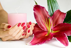 Manicure, cnadle and lily Stock Photos