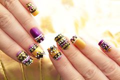 Manicure with colorful ethnic design. With rhinestones on female hand close up on colorful background royalty free stock photography