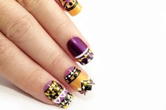 Manicure with colorful ethnic design. With rhinestones on female hand close up on colorful background royalty free stock photo